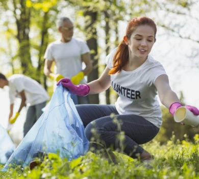 girl volunteering and cleaning up trash in a park | Century 21 Action