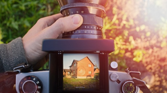 camera with house for sale on screen | Century 21 Action