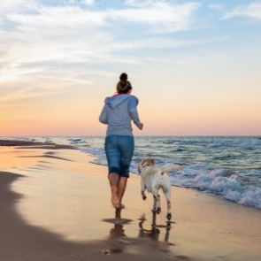 Woman running on the beach with her dog | Century 21 Topsail Island Real Estate